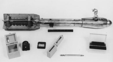 A bathythermograh (top) and its accessories. The glass slide (right) was smoked with skunk oil and inserted into the body of the instrument. During a cast, temperature changes caused the length of copper coil at the tail to expand or contract, moving a lever that etched the oil on the slide. A technician would then read the etching using a loupe to magnify the record. This was quite a skill, especially in rough winter seas, I'm told.